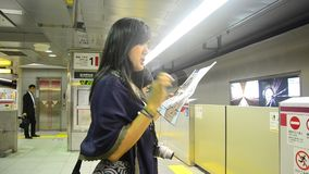Traveler thai women read and looking map for use subway marunouchi line. TOKYO, JAPAN - OCTOBER 21 : Traveler thai women read and looking map for use subway stock video