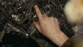 The traveler tirogaet hand in the mine deposits of mica. Close-up of a hand with mica deposits. 4K stock video footage