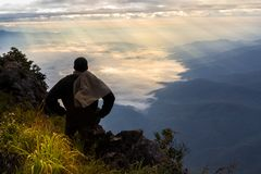A traveler on top of mountain, he sitting on the rock royalty free stock photography