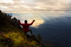 A traveler on top of mountain. He standing on the rock watching a nice sunrise Stock Photo