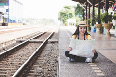 Traveler and tourist asian young women wearing backpack holding map, waiting for a train. Traveler and tourist asian young woman wearing backpack holding map Stock Image
