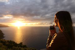 Traveler tourist girl taking photo in a sunset on the vacations Royalty Free Stock Images
