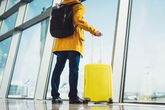 Traveler tourist with yellow suitcase backpack is standing at airport on background large window, man in bright jacket waiting. In departure lounge area hall of stock photography