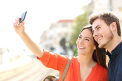 Traveler tourists couple photographing a selfie. In a train station Royalty Free Stock Photo