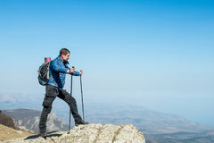 Traveler with trekking sticks and a backpack on the top of the mountain Royalty Free Stock Photo