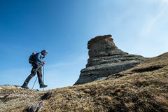 Traveler with trekking sticks and a backpack walks in the mounta Stock Images