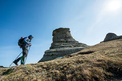 Traveler with trekking sticks and a backpack walks in the mounta Stock Photography