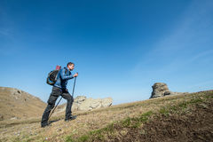 Traveler with trekking sticks and a backpack walks in the mountains Royalty Free Stock Images