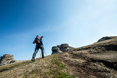 Traveler with trekking sticks and a backpack walks in the mountains Royalty Free Stock Photography
