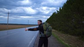 The traveler is trying to stop the car in cloudy weather. A tourist hitchhiker walks along the road with a backpack on his shoulders, lifting his thumb up stock video footage