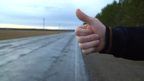 The traveler is trying to stop the car in cloudy weather. A tourist hitchhiker walks along the road with a backpack on his shoulders, lifting his thumb up stock footage