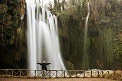Traveler under waterfall Stock Images