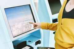 Traveler using a self check-in machine kiosk service at airport. royalty free stock photography