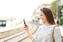 Traveler using a smartphone in a train station. Happy traveler using a smartphone in a train station while is waiting for transport Royalty Free Stock Image