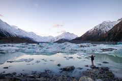A traveler viewing the icebergs and snow mountains New Zealand. A traveler viewing the amazing icebergs and snow mountains during dusk in Tasman Valley, New stock photos