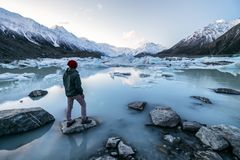A traveler viewing the amazing icebergs and snow mountains in Tasman Valley, New Zealand. A traveler viewing the amazing icebergs and snow mountains during dusk stock images