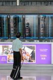 A traveler views a departures board at Suvanaphumi Airport. BANGKOK - JUNE 21 : A traveler views a departures board at Suvanaphumi Airport, Bangkok on JUNE 21 Royalty Free Stock Photos