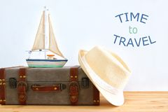 Traveler vintage luggage, boat and fedora hat over wooden table. holiday and vacation concept. Traveler vintage luggage, boat and fedora hat over wooden table Royalty Free Stock Images