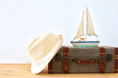 Traveler vintage luggage, boat and fedora hat over wooden table. holiday and vacation concept. Traveler vintage luggage, boat and fedora hat over wooden table Royalty Free Stock Photos