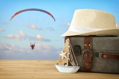 Traveler vintage luggage, boat and fedora hat over wooden table infront of parachute in the sky. holiday and vacation concept. Traveler vintage luggage, boat Stock Photos