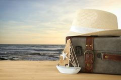 Traveler vintage luggage, boat and fedora hat over wooden table infront of sea landscape. holiday and vacation concept. Traveler vintage luggage, boat and Stock Photography