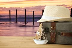 Traveler vintage luggage, boat and fedora hat over wooden table infront of sea landscape. holiday and vacation concept. Traveler vintage luggage, boat and Stock Photos