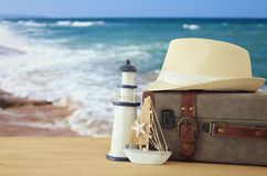 Traveler vintage luggage, boat and fedora hat over wooden table infront of sea landscape. holiday and vacation concept. Traveler vintage luggage, boat and Royalty Free Stock Photo