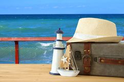 Traveler vintage luggage, boat and fedora hat over wooden table infront of sea landscape. holiday and vacation concept. Traveler vintage luggage, boat and Stock Photo