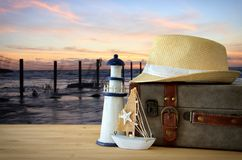 Traveler vintage luggage, boat and fedora hat over wooden table infront of sea landscape at sunset. holiday and vacation concept. Traveler vintage luggage, boat Royalty Free Stock Photography