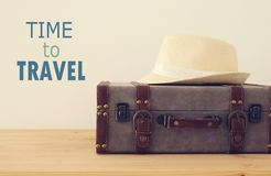 Traveler vintage luggage, camera and fedora hat over wooden table. holiday and vacation concept. Traveler vintage luggage, camera and fedora hat over wooden Stock Photography