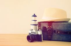Traveler vintage luggage, camera and fedora hat over wooden table. holiday and vacation concept. Traveler vintage luggage, camera and fedora hat over wooden Stock Photo
