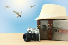 Traveler vintage luggage, camera and fedora hat over wooden table infront of blue sky and birds. holiday and vacation concept. Traveler vintage luggage, camera Royalty Free Stock Photography
