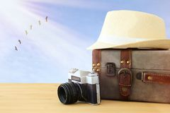 Traveler vintage luggage, camera and fedora hat over wooden table infront of blue sky and birds. holiday and vacation concept. Traveler vintage luggage, camera Stock Images