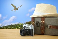 Traveler vintage luggage, camera and fedora hat over wooden table infront of blue sky and birds. holiday and vacation concept. Traveler vintage luggage, camera Stock Photos