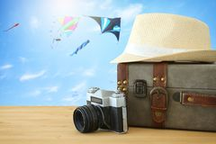 Traveler vintage luggage, camera and fedora hat over wooden table infront of blue sky and colorful kite. holiday and vacation conc. Ept Stock Photography