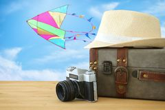 Traveler vintage luggage, camera and fedora hat over wooden table infront of blue sky and colorful kite. holiday and vacation conc. Ept Royalty Free Stock Images