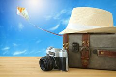 Traveler vintage luggage, camera and fedora hat over wooden table infront of blue sky and colorful kite. holiday and vacation conc. Ept Stock Images