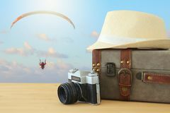 Traveler vintage luggage, camera and fedora hat over wooden table infront of blue sky and parachute sport. holiday and vacation co. Ncept Royalty Free Stock Image