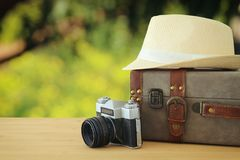 Traveler vintage luggage, camera and fedora hat over wooden table infront of bokeh landscape. holiday and vacation concept. Traveler vintage luggage, camera and Stock Image