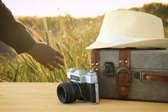 Traveler vintage luggage, camera and fedora hat over wooden table infront of a field at sunset light. Holiday and vacation concept Royalty Free Stock Images