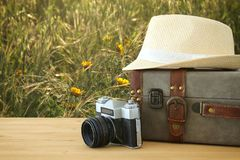 Traveler vintage luggage, camera and fedora hat over wooden table infront of a field at sunset light. Holiday and vacation concept Stock Photography