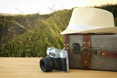 Traveler vintage luggage, camera and fedora hat over wooden table infront of a field at sunset light. Holiday and vacation concept Stock Photos