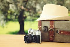 Traveler vintage luggage, camera and fedora hat over wooden table infront of a field at sunset light. Traveler vintage luggage, camera and fedora hat over Royalty Free Stock Photography