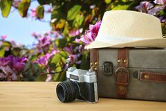 Traveler vintage luggage, camera and fedora hat over wooden table infront of a field at sunset light. Traveler vintage luggage, camera and fedora hat over Royalty Free Stock Image