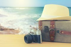 Traveler vintage luggage, camera and fedora hat over wooden table infront of sea landscape. holiday and vacation concept. Traveler vintage luggage, camera and Royalty Free Stock Photography