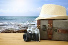 Traveler vintage luggage, camera and fedora hat over wooden table infront of sea landscape. holiday and vacation concept. Traveler vintage luggage, camera and Royalty Free Stock Images