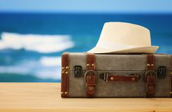 Traveler vintage luggage and fedora hat over wooden table. holiday and vacation concept. Traveler vintage luggage and fedora hat over wooden table. holiday and Stock Photos
