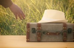 Traveler vintage luggage and fedora hat over wooden table. holiday and vacation concept. Traveler vintage luggage and fedora hat over wooden table. holiday and Stock Photo