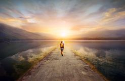 Traveler walking along the road to the mountains.  stock photo