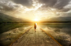 Traveler walking along the road to the mountains.  royalty free stock photos